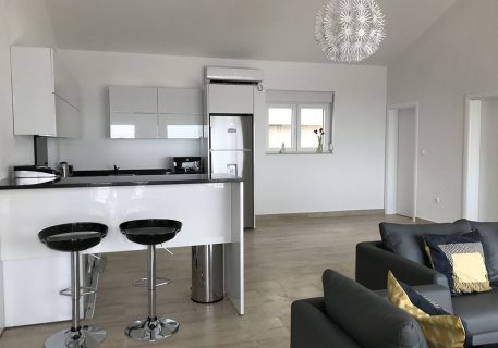 Villa Leni-Open plan lounge area with bar unit and stools opening into the kitchen area