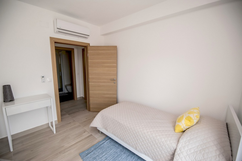 Villa Layla-Twin bedroom with built-in wardrobes and access onto the balcony. AC